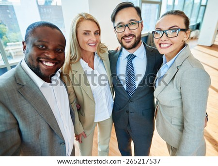 Happy business partners in formalwear looking at camera in office - stock photo