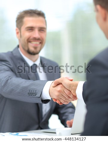 Happy business partners shaking hands in an office - stock photo