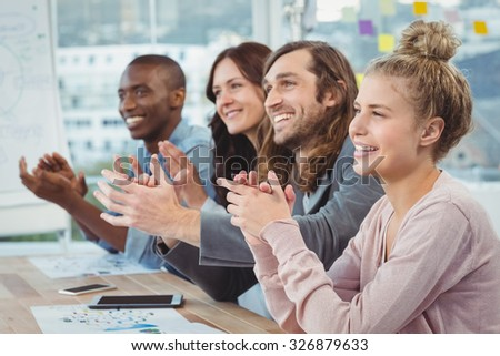 Happy business people clapping at desk in office - stock photo