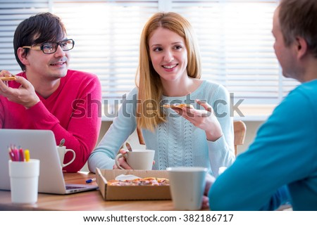 Happy business People Having Meeting And Eating Pizza in office.  Three young cheerful colleagues having lunch together at work. Creative team around table - stock photo