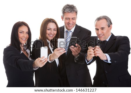 Happy Business People Looking At Cell Phones Over White Background - stock photo