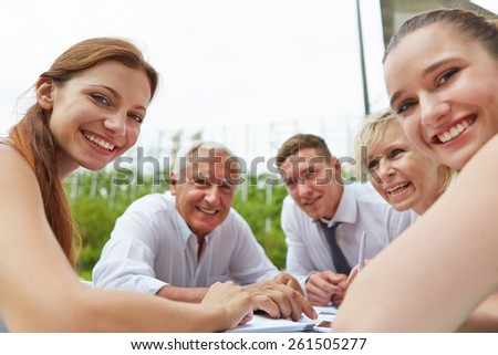 Happy business people sitting together during meeting outdoors on a table - stock photo