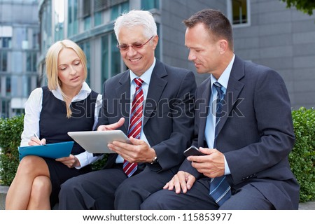 Happy business people team working on a tablet computer - stock photo