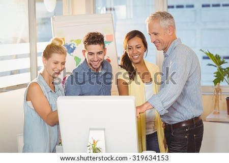 Happy business people using computer in meeting room at creative office - stock photo