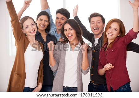 Happy business team. Group of cheerful young people standing close to each other and keeping arms raised - stock photo