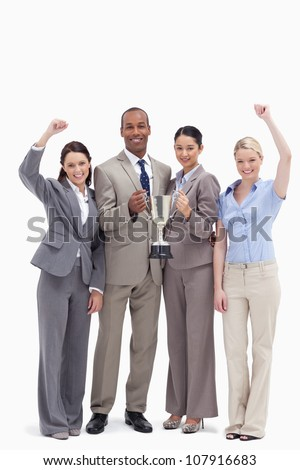 Happy business team holding a cup and raising arms against white background - stock photo