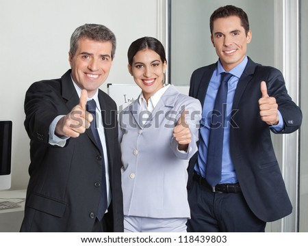 Happy business team in the office holding their thumbs up - stock photo