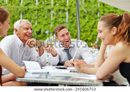 Happy business team laughing during planning in a meeting outdoors - stock photo
