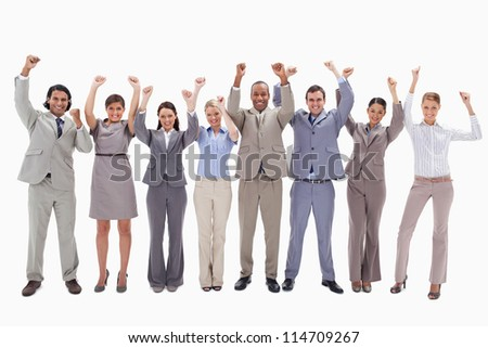 Happy business team raising their arms against white background - stock photo