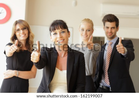 Happy business team showing thumbs up in the office - stock photo