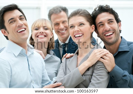Happy business team smiling and laughing together at office - stock photo