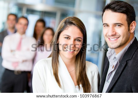 Happy business team smiling at the office - stock photo
