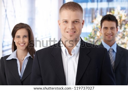 Happy business team standing in office, focus on smiling young businessman looking at camera. - stock photo
