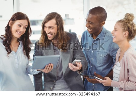 Happy business team using technology while standing at office - stock photo