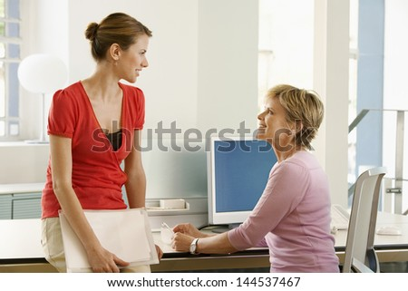 Happy business woman discussing at office desk - stock photo