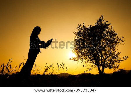 Happy Business woman holding laptop  at sunset silhouette. - stock photo