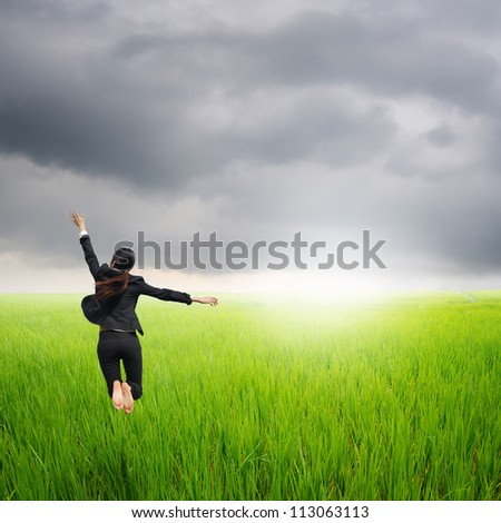 Happy business woman jumping in green rice field and rainclouds - stock photo