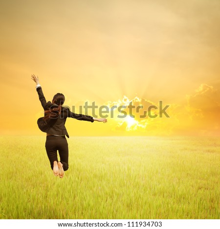 Happy Business woman jumping to sunset in grassland - stock photo