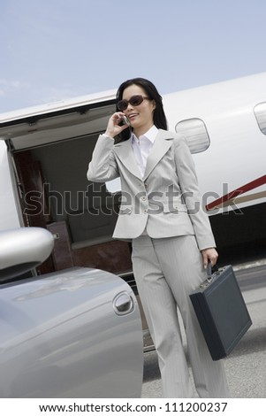 Happy business woman on a call standing by car with plane in the background at airfield - stock photo