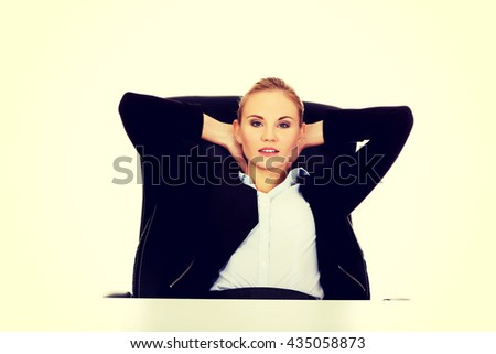 Happy business woman relaxing in office - stock photo