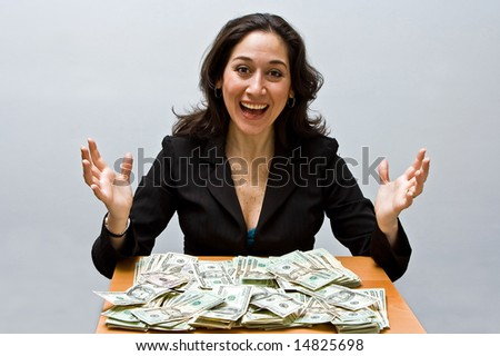 Happy business woman sitting at a table covered with stacks of money isolated on a white background - stock photo