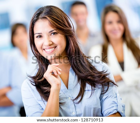 Happy business woman smiling at the office - stock photo
