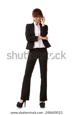 Happy business woman talking on cellphone, full length portrait isolated on white background. - stock photo