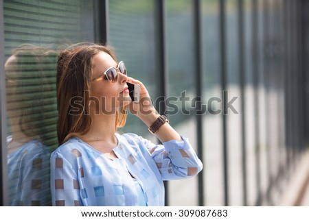 Happy business woman talking on the phone outdoors. Pretty lady in sunglasses leaning on the wall of the office building. She is looking away. - stock photo