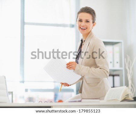 Happy business woman working in office with documents - stock photo