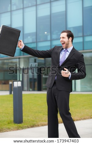 happy businessman after a good day in front of an office building  - stock photo