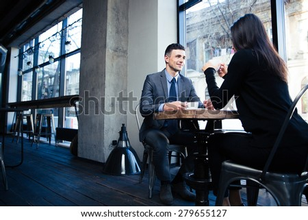 Happy businessman and businesswoman sitting at the table with coffee in restaurant - stock photo