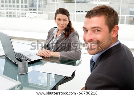 Happy businessman and businesswoman working together on a laptop during a meeting - stock photo