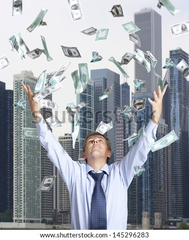 Happy businessman and flying dollar banknotes against skyscrapers - stock photo