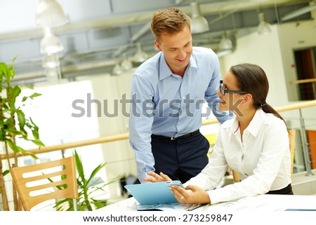 Happy businessman consulting with secretary by workplace at meeting - stock photo