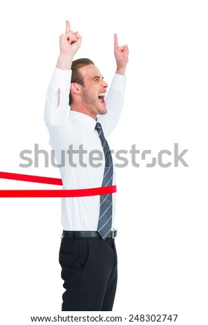 Happy businessman crossing the finish line and pointing up on white background - stock photo