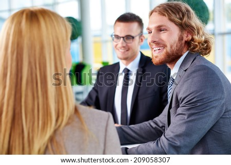 Happy businessman explaining his idea to partners at meeting - stock photo