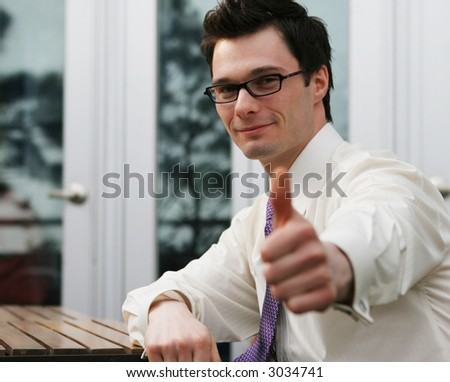 Happy businessman gives the thumbs up gesture. - stock photo