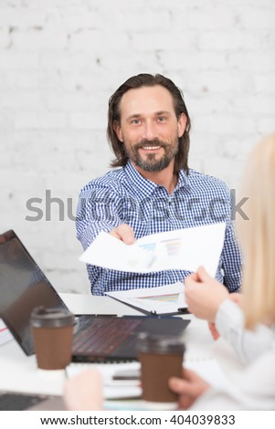Happy businessman giving sheet of paper to his colleague in office. Happy bearded man smiling for camera while working. - stock photo