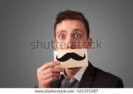 Happy businessman holding funny mustache card on his mouth with gradient background - stock photo