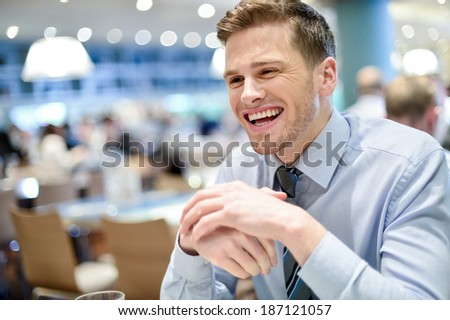 Happy businessman in a restaurant and smiling - stock photo