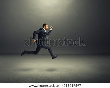 happy businessman in formal wear running over dark background - stock photo