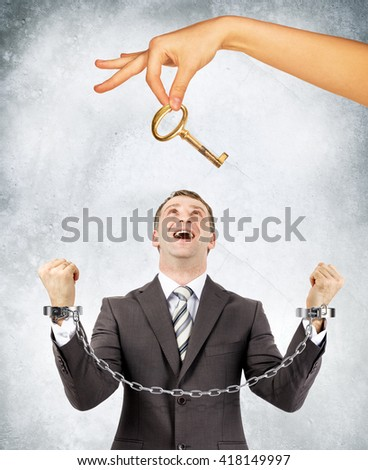 Happy businessman in handcuffs and big hand offering key - stock photo