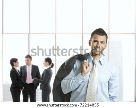 Happy businessman in office lobby smiling at camera, businesspeople talking in background.? - stock photo