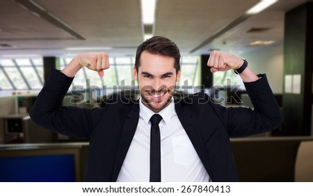 Happy businessman in suit cheering against empty office with separate units - stock photo