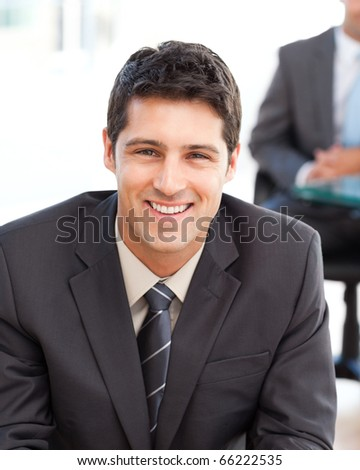 Happy businessman in the foreground during a meeting with a friend at the office - stock photo