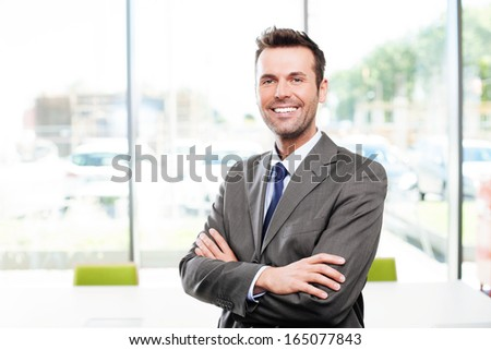 Happy businessman in the office standing with crossed arms - stock photo