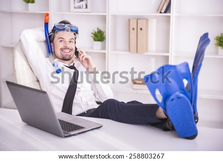 Happy businessman is working in office is wearing in fins. - stock photo