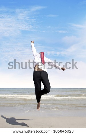 Happy businessman jumping at the beach to celebrate his success - stock photo