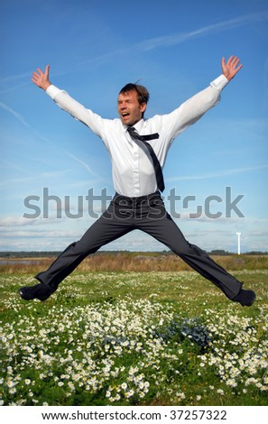 Happy businessman jumping in a field of daisy - stock photo