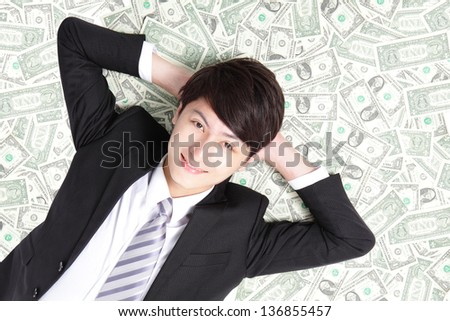 happy businessman lying on heap of dollars and smiling - stock photo